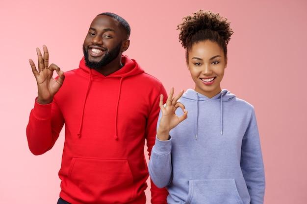 2人のアフリカ系アメリカ人の巧みな同僚の専門家が友人にすべての完璧な笑顔を保証しました広く喜んでうなずき同意ジェスチャーショー大丈夫ok悪い選択サイン、ピンクの背景