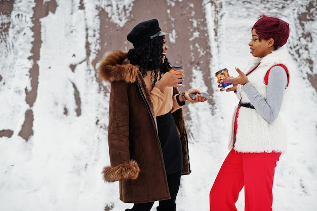 Two african american women in sheepskin and fur coat posed at winter day against snowy background with cups
