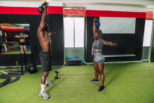 ジムでケトルベルを使って上腕二頭筋と肩の調子を整えるエクササイズをしている2人のアフリカのボディービルダーアスリート。クロスフィットトレーニングルーチンを行うアフリカのボディービルダー