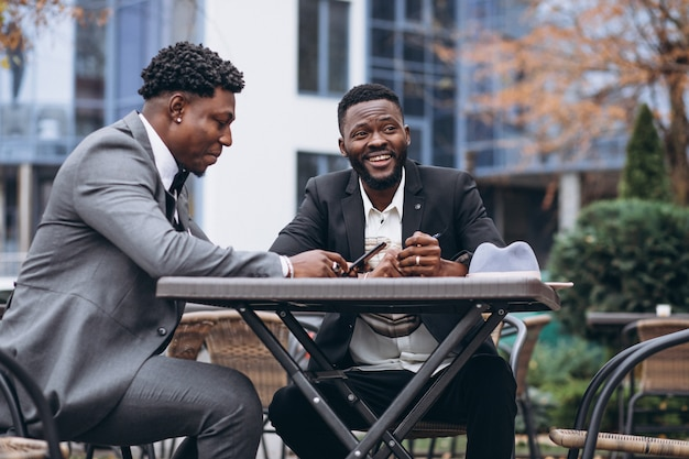 Two african businessman sitting outside cafe