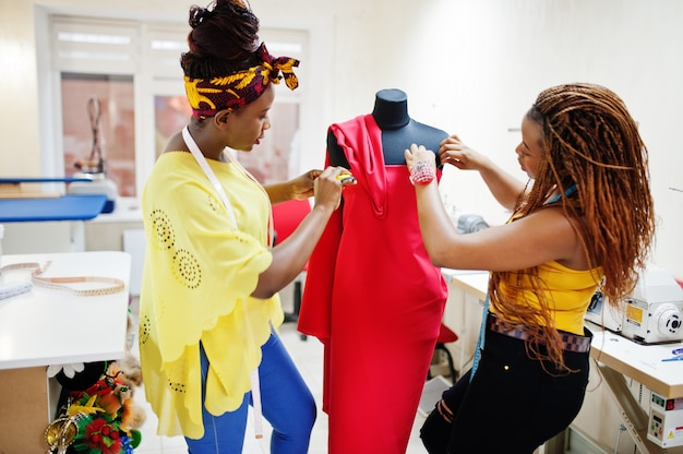 Two african dressmaker woman designed new red dress on mannequin at tailor office. black seamstress girls.