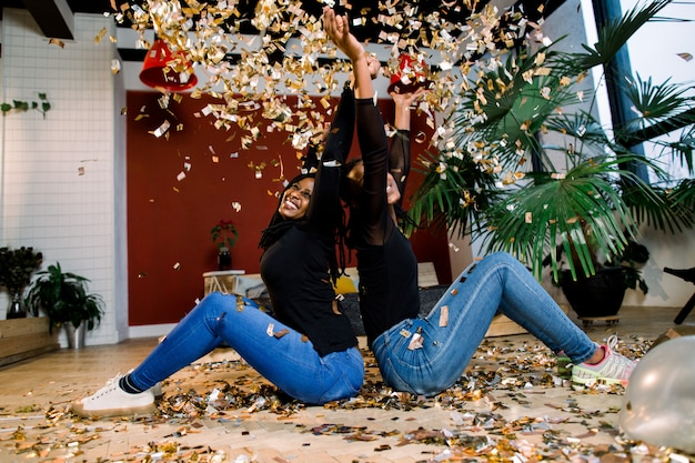 Two african girls, happy stylish friends celebrating new year or birthday party sit back with each other and throw a confetti. fashion elegance women enjoying time together.