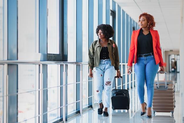 空港でスーツケースを持つ2つのアフリカの女の子旅行や休暇の概念