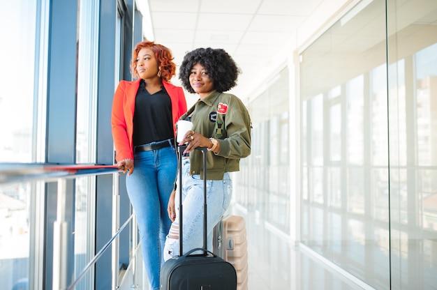 空港でスーツケースを持つ2つのアフリカの女の子