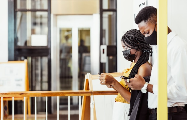 Two african students with mask using their mobile phones on campus