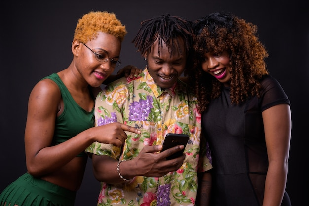 Two african woman and one african man together on black