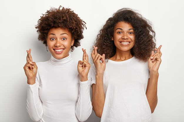 Two afro american female students cross fingers, believe in good luck and getting excellent mark on exam, smile happily
