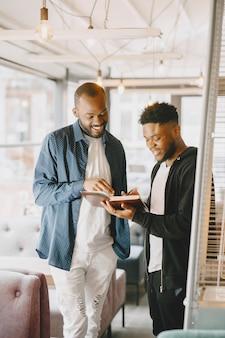 会話をしている2人のアフリカ系アメリカ人男性。カフェに座っている友達。