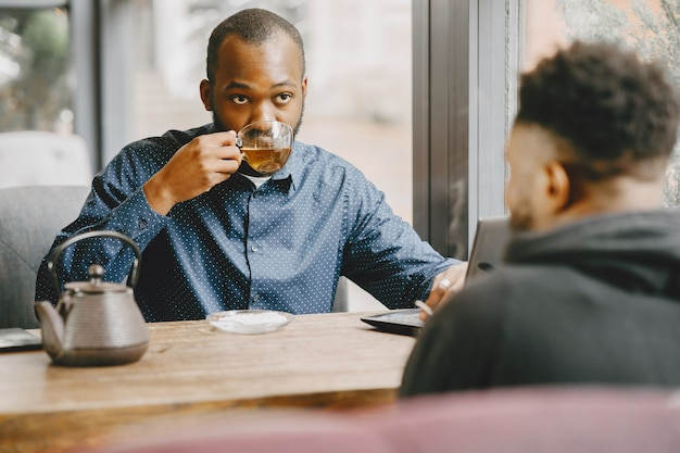 Two afro-american men having a conversation with a cup of tea. friend sitting in a cafe.