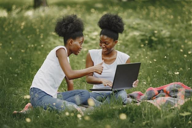 두 명의 아프리카계 미국인 자매가 공원에서 휴식을 취하고 있습니다.