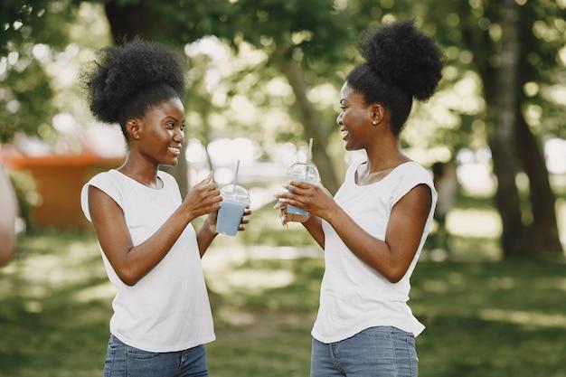 2人のアフリカ系アメリカ人の姉妹が公園で休んでいます