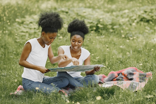 公園の地図で見ている2人のアフリカ系アメリカ人の姉妹