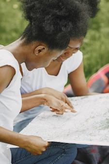 Due sorelle afroamericane che guardano in una mappa in un parco