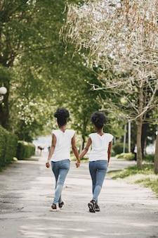2人のアフリカ系アメリカ人の姉妹が公園で休憩し、手をつないでいます