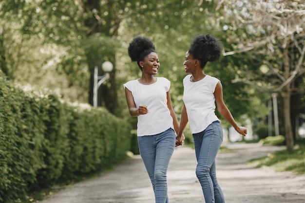 두 명의 아프리카계 미국인 자매가 공원에서 손을 잡고 휴식을 취하고 있습니다.