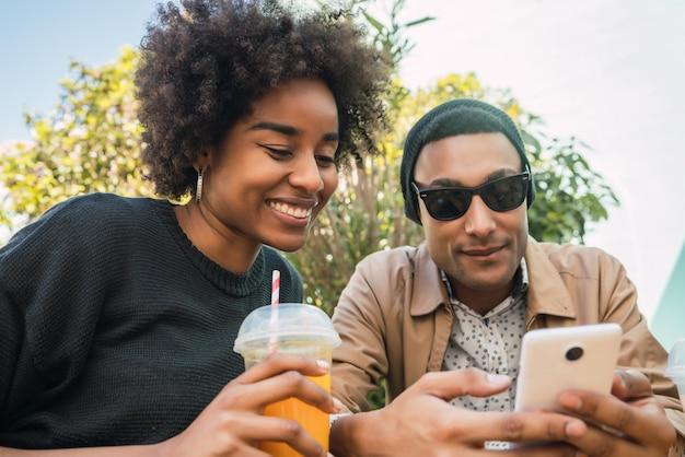 Два друга афро с помощью своего мобильного телефона