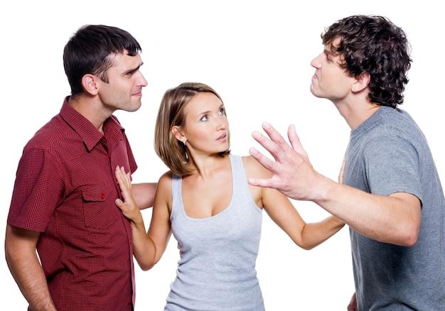 Два агрессивных мужчины борются за женщину, изолированную на белом