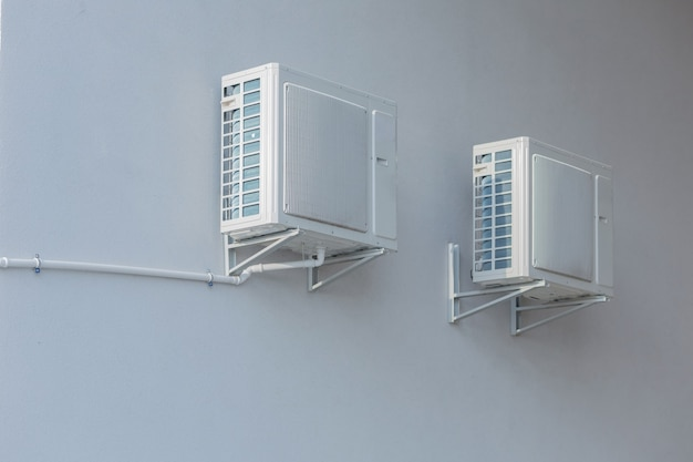 Two air conditioning fans are mounted on a white wall
