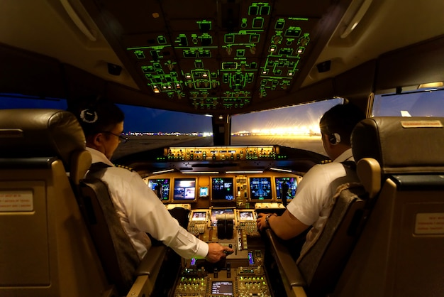 Two airline pilots are starting the airplane engines at night time.