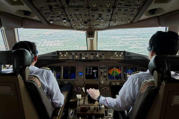 Two airliner pilots are controlling the airplane towards the runway.