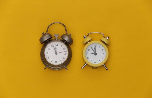 黄色の背景に2つの目覚まし時計。