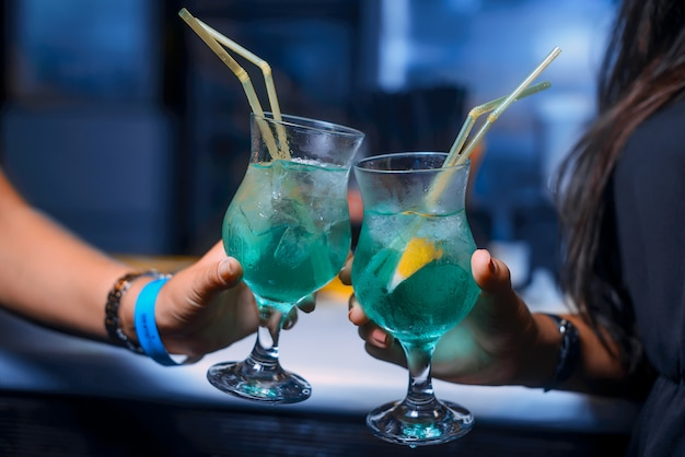 Two alcohol cocktails keeping in girls hands in the night club