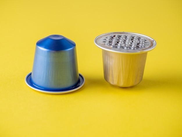 黄色の背景に挽いたコーヒーと2つのアルミニウムカプセル。それらの1つが使用されます。側面図、製品の保管と再利用のための最新ソリューションの概念