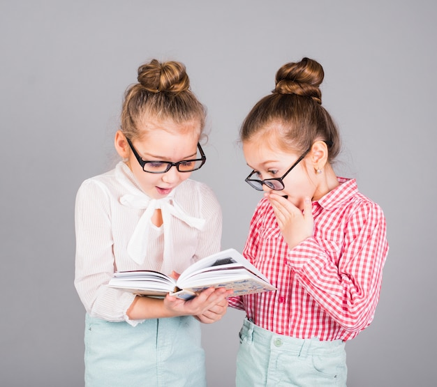 Two amazed girls in glasses reading book