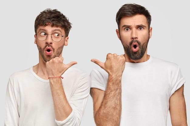 2人の驚いた男はお互いに指示し、愚かな表情をし、顎を落とし続け、壁のあるトーンのカジュアルな白いtシャツを着ています