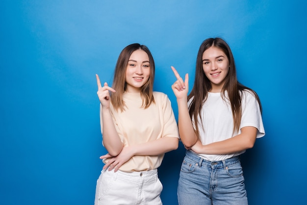 Two amazed mixed race women point with index fingers upwards, have happy expressions, isolated on blue wall.