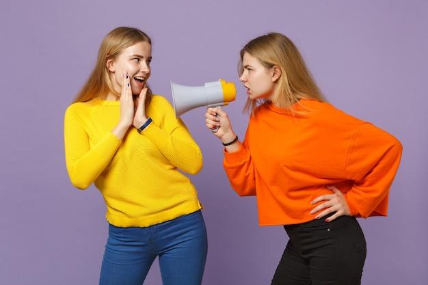 パステルバイオレットブルーの壁に隔離されたメガホンで、鮮やかなカラフルな服を着た2人の驚いたショックを受けた若いブロンドの双子の姉妹の女の子が悲鳴を上げます。人々の家族のライフスタイルの概念。 。