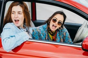 Two amazed women looking out from car window