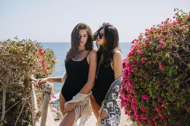 Две удивительные девушки в одинаковых одеждах стоят между цветущими кустами на горизонте. веселые сестры с длинными волосами в стильных черных купальниках вместе позируют на летних каникулах