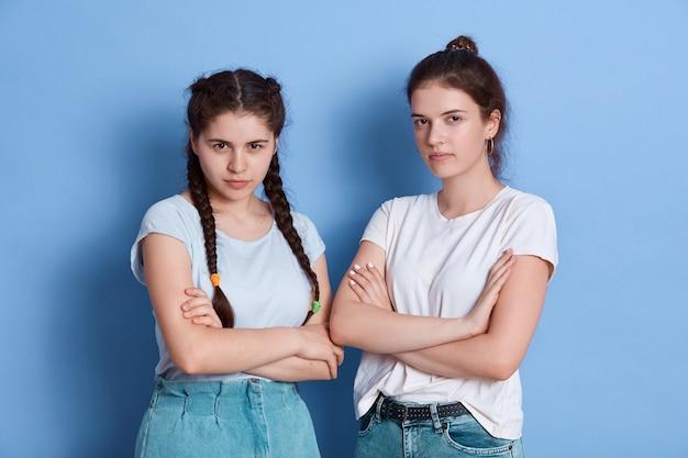 Две удивительные дамы стоят с сердитыми выражениями лиц