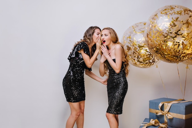 Two amazing young women in black stylish dresses having fun on blue space. gossip girl, whispering, expressing true emotions, surprised