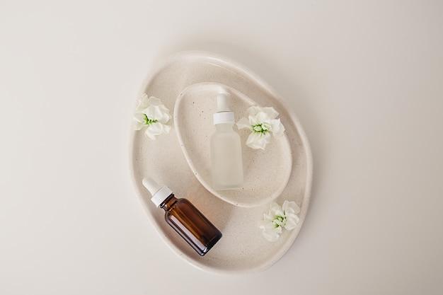 化粧品、自然医学、白い背景に花で飾られたアボカド形のセラミックプレート内のエッセンシャルオイル用の2つの琥珀色とマットなガラス瓶。上面図、美容製品フラットレイ。