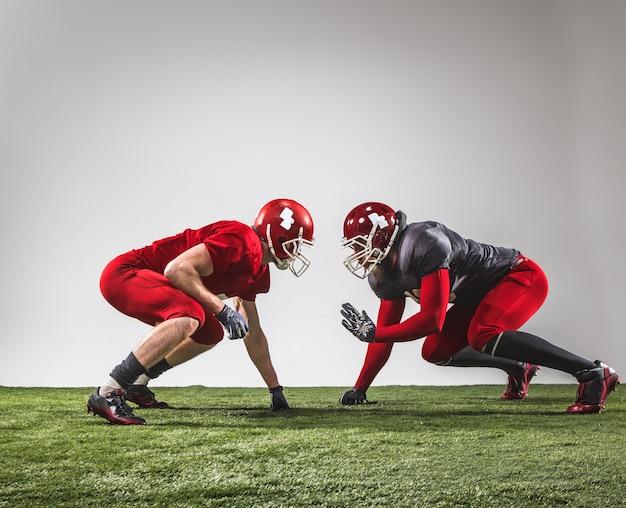 I due giocatori di football americano in azione su erba verde e sfondo grigio.