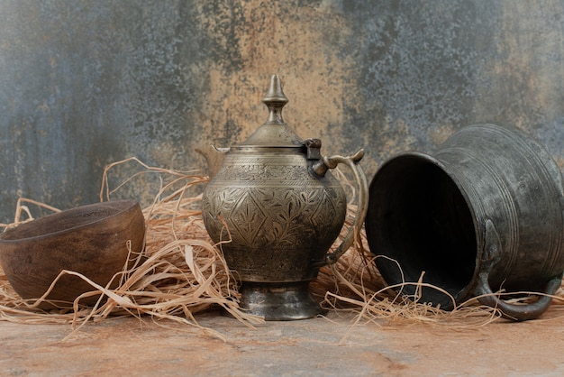 Two ancient kettles with empty wooden plate on burlap.