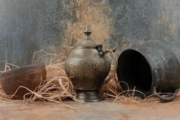 Due antichi bollitori con piatto di legno vuoto su tela da imballaggio.