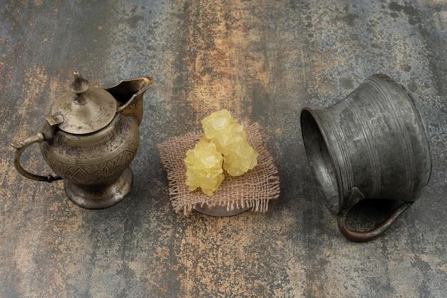 대리석 표면에 달콤한 설탕 조각 두 고대 주전자.