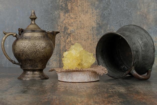 大理石の表面に甘い砂糖のスライスが付いた2つの古代のやかん。