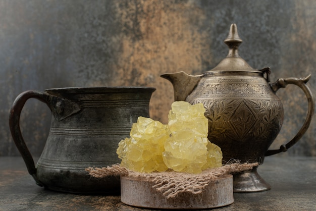 Два древних чайника с кусочками сладкого сахара на мраморной стене.