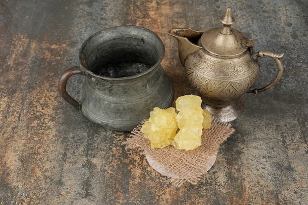 Two ancient kettles with slices of sweet sugar on marble surface.