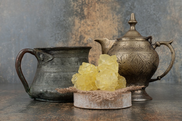 Two ancient kettles with slices of sweet sugar on marble wall.