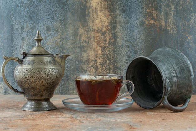 Two ancient teapots with herbal tea on marble background