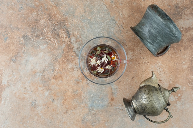 Два древних чайника с травяным чаем на мраморном фоне