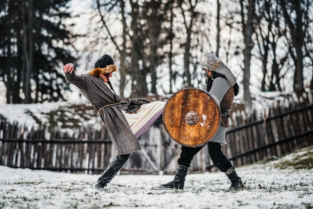 Two ancient warriors in armor with weapons fighting with swords in the snow