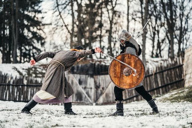 雪の中で剣と戦う武器を持つ鎧を着た2人の古代の戦士