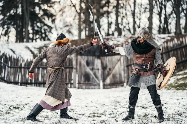 Два древних воина в доспехах с оружием сражаются с мечами на снегу