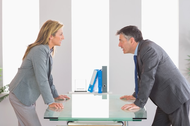 Two angry businesspeople arguing on each side of desk